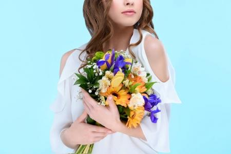 Photo for Cropped shot of young woman holding floral bouquet isolated on blue - Royalty Free Image