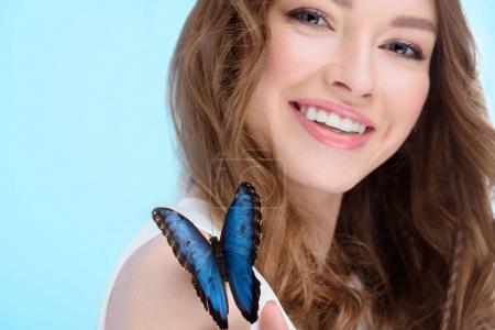 Photo pour Jeune femme souriante avec papillon sur l'épaule isolé sur bleu - image libre de droit