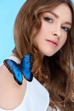 Photo for Attractive young woman with butterfly on shoulder isolated on blue - Royalty Free Image