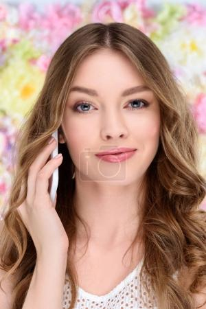 Photo for Close-up portrait of smiling young woman talking by phone on floral background - Royalty Free Image