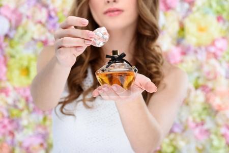 Photo pour Recadrée tir de bouteille ouverture femme de parfum sur fond floral - image libre de droit
