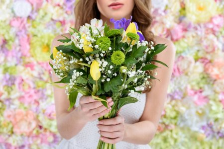 cropped shot of young woman holding floral bouquet