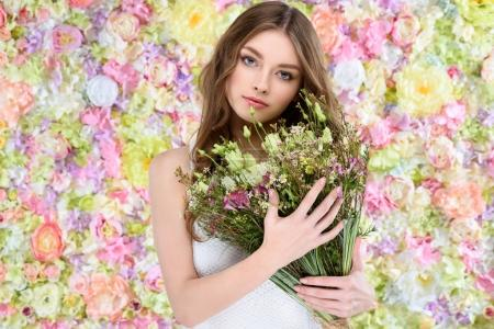 attractive young woman holding floral bouquet