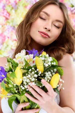 close-up portrait of beautiful young woman holding floral bouquet