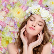 Sensual young woman in floral wreath with perfect skin