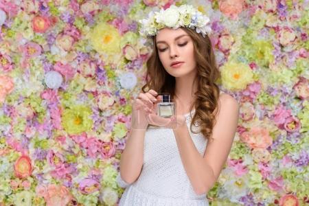 Photo pour Belle jeune femme en couronne florale avec une bouteille de parfum - image libre de droit