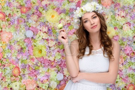 beautiful young woman in floral wreath with blossoming rose bud