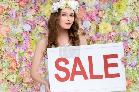 Photo for Beautiful young woman in floral wreath with sale board - Royalty Free Image