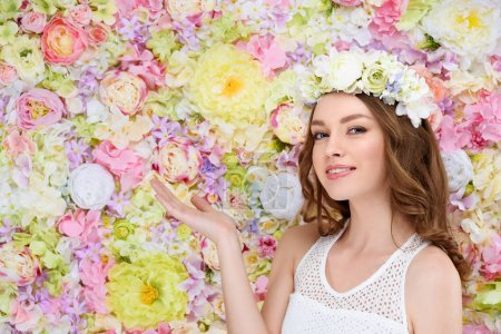 happy young woman in floral wreath pointing at copy space