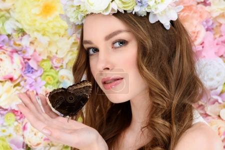 beautiful young woman in floral wreath holding butterfly
