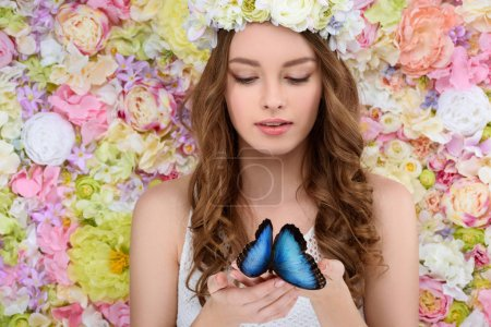 attractive young woman in floral wreath holding blue butterfly