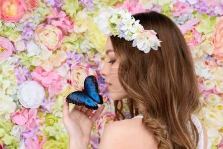 young woman in floral wreath with butterfly on hand