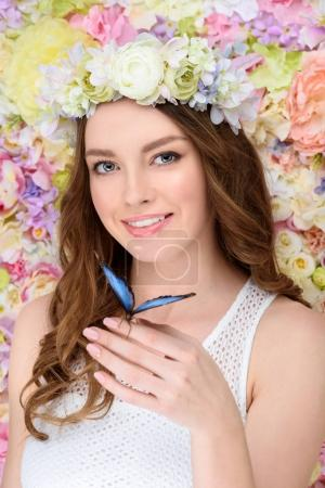 happy young woman in floral wreath with butterfly on hand