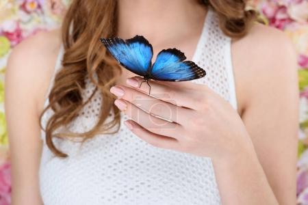 Photo pour Plan recadré de femme avec beau papillon bleu à portée de main - image libre de droit