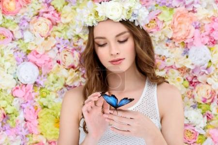 sensual young woman in floral wreath with butterfly on hand