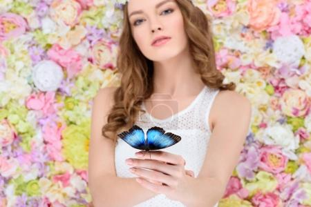 attractive young woman in floral wreath with butterfly on hand