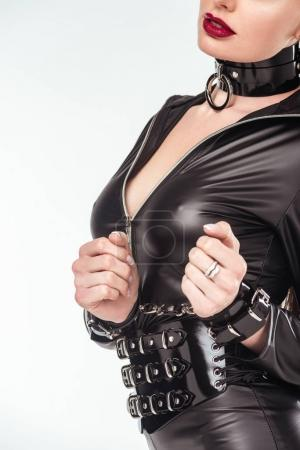 Seductive young woman in leather suit and cuffs isolated on white