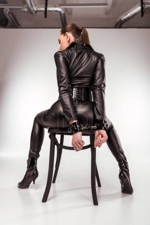 Kinky woman in sexy costume in handcuffs sitting on chair on white background