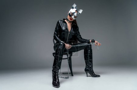 Kinky woman in sexy costume sitting on chair and holding chain on grey background