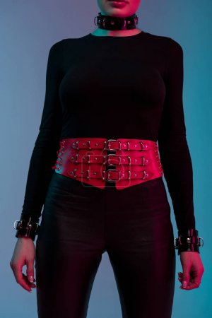 Kinky woman in sexy costume with wide red belt isolated on blue