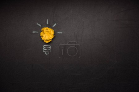 Photo for Light bulb symbol made of crumpled paper on blackboard - Royalty Free Image