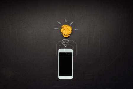 Photo for Digital smartphone and light bulb symbol isolated on blackboard - Royalty Free Image
