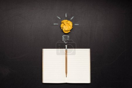 Photo for Light bulb symbol and blank notebook with pencil on blackboard - Royalty Free Image