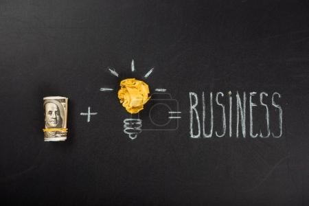 Photo for Business concept made of light bulb symbol and money on blackboard - Royalty Free Image