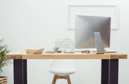 Photo for Empty workplace with computer screen, notebooks and coffee cup in office - Royalty Free Image