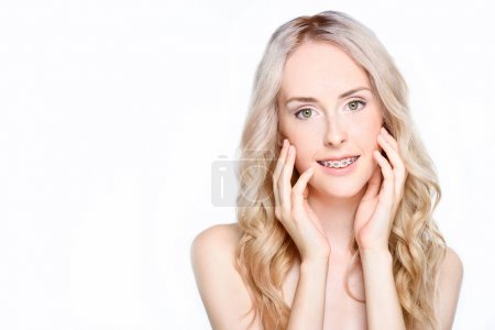 Woman with braces touching face