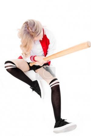 Woman sitting and holding baseball bat