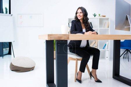 Photo pour Heureuse femme enceinte assis au milieu de travail dans le bureau moderne - image libre de droit