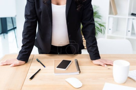 Pregnant businesswoman leaning on desk