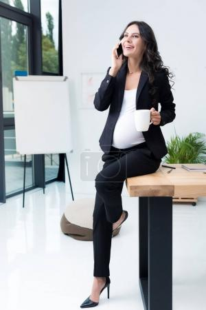 pregnant businesswoman talking by phone