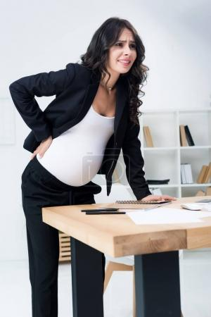 pregnant businesswoman with back pain