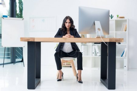 serious pregnant businesswoman at workplace