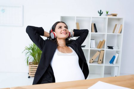 pregnant businesswoman relaxing and listening music
