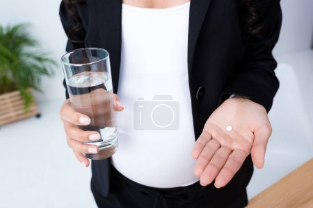 Pregnant businesswoman with glass of water and pills