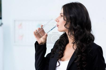 Photo for Side view young businesswoman drinking water - Royalty Free Image