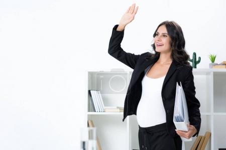 Pregnant businesswoman waving hand