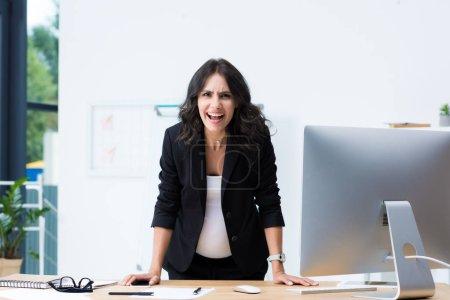 pregnant businesswoman screaming at camera