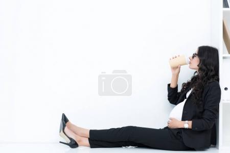 pregnant businesswoman drinking coffee