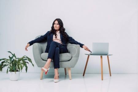 businesswoman relaxing in armchair