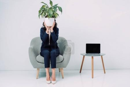 businesswoman covering face with flower pot