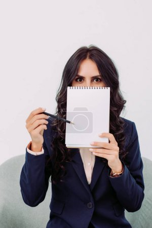 businesswoman covering face with notepad