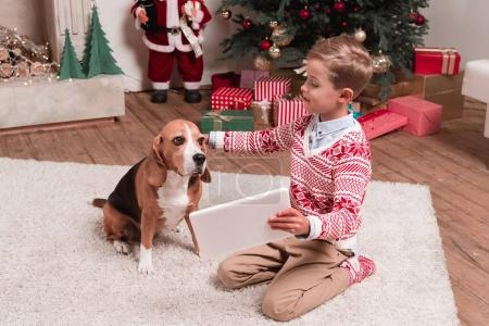boy showing tablet to dog on christmas