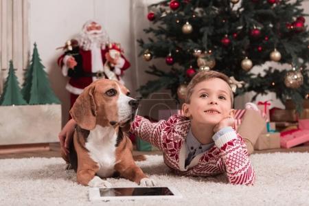 Photo pour Heureux garçon avec beagle chien couché sur le sol de Noël chambre décorée - image libre de droit