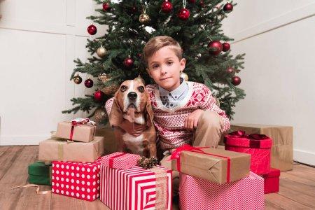 boy with dog under christmas tree