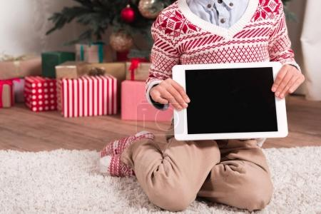 boy with tablet next to christmas tree