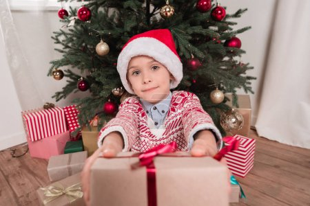 boy giving christmas present to camera
